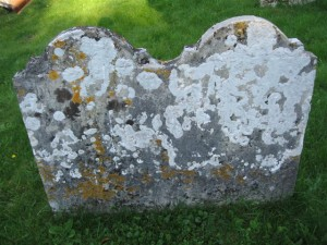 A lichen-encrusted headstone in the graveyard